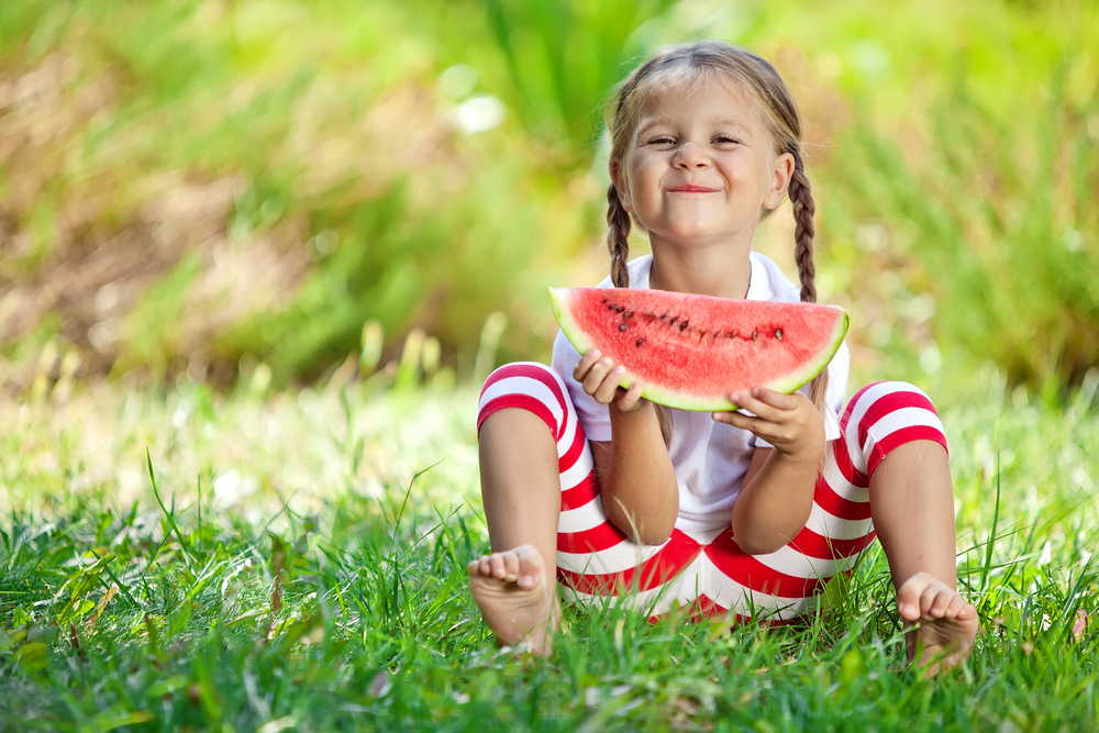 happy girl eating watermelon in grass