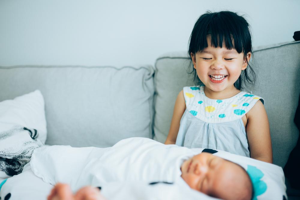 Little sister hugging her newborn brother.